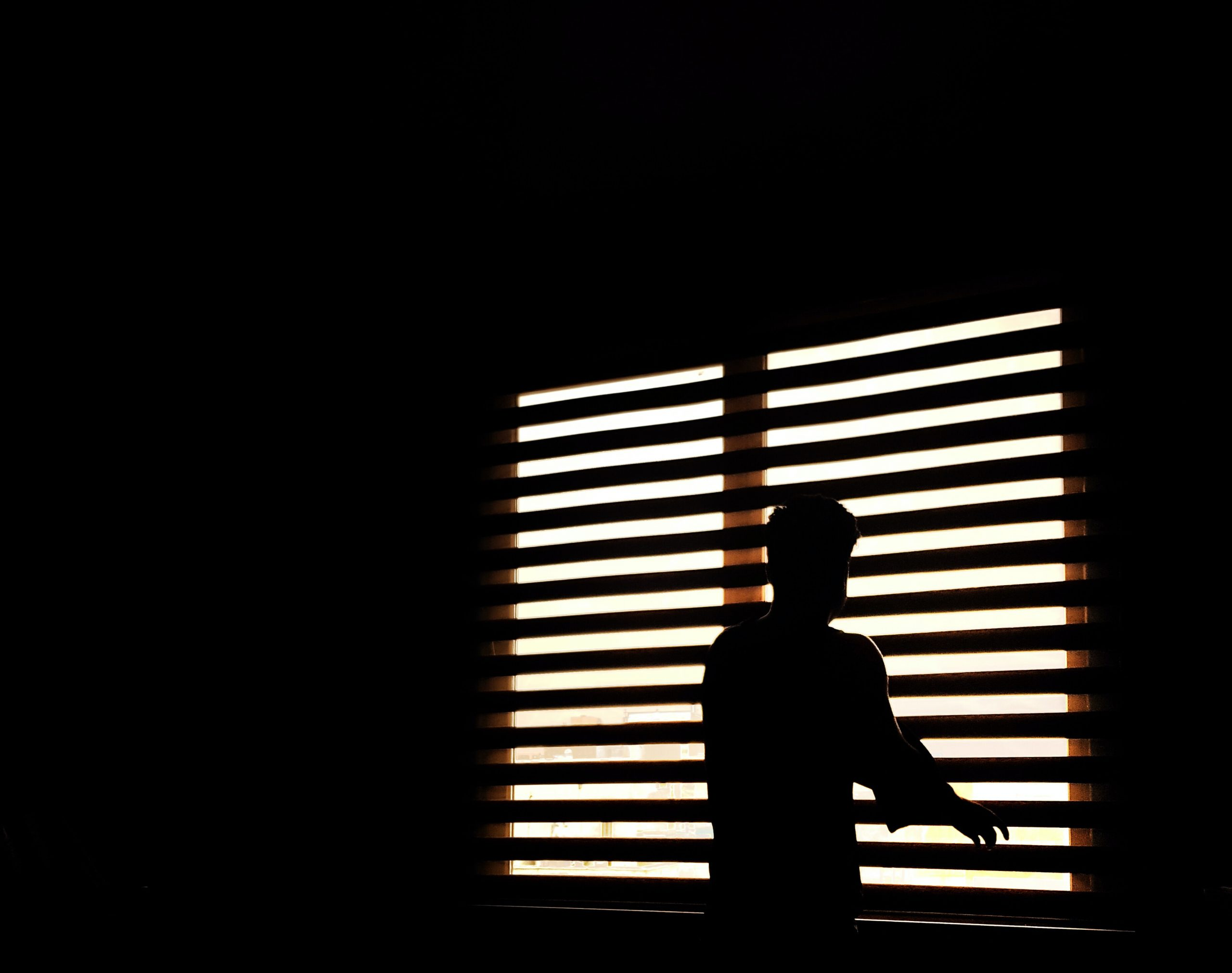 Silhouette of a man at window shades in the dark.