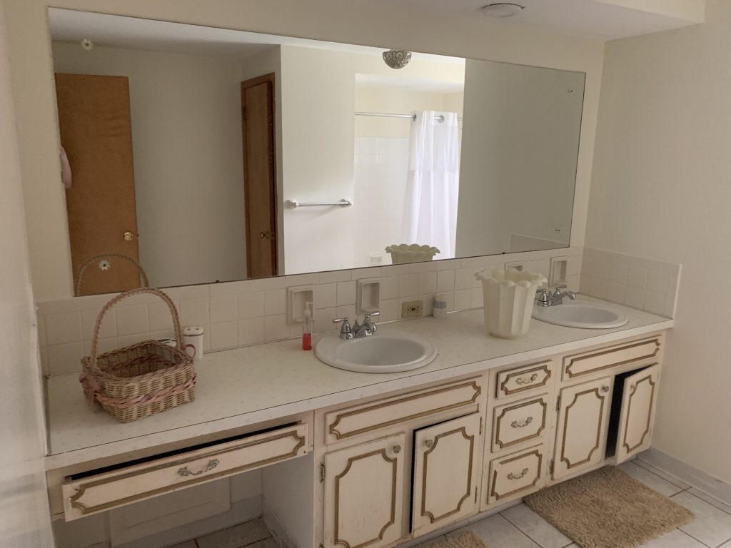 A bathroom with a rectangular mirror the length of the counter.