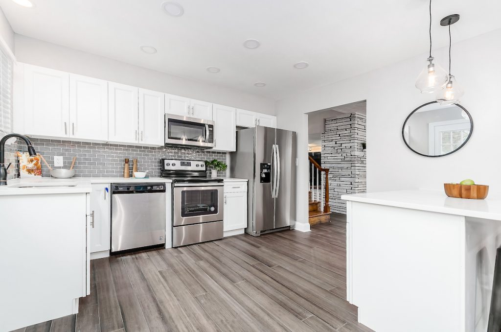 A kitchen with a small mirror, stainless steel appliances, and nice flooring.