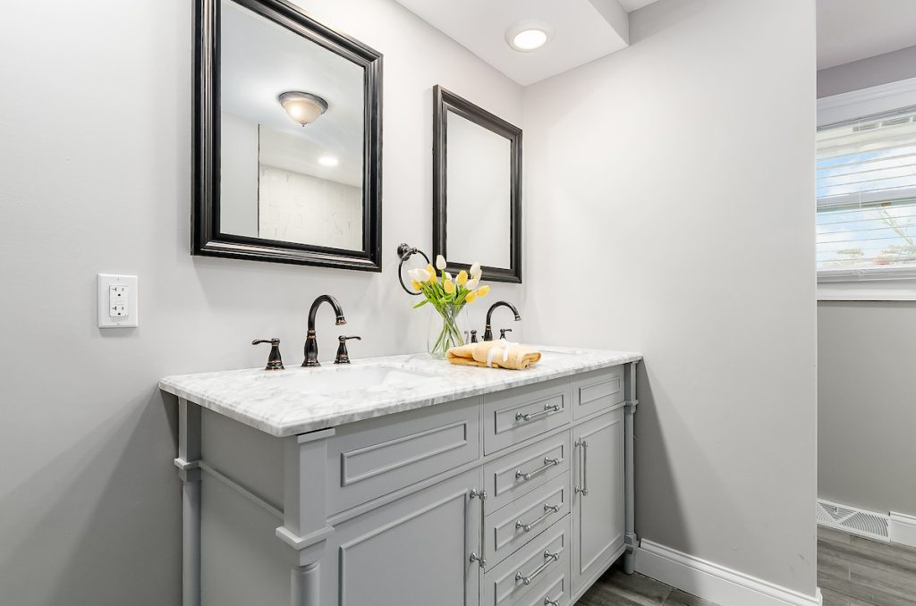 A double vanity sink with two mirrors above each sink.