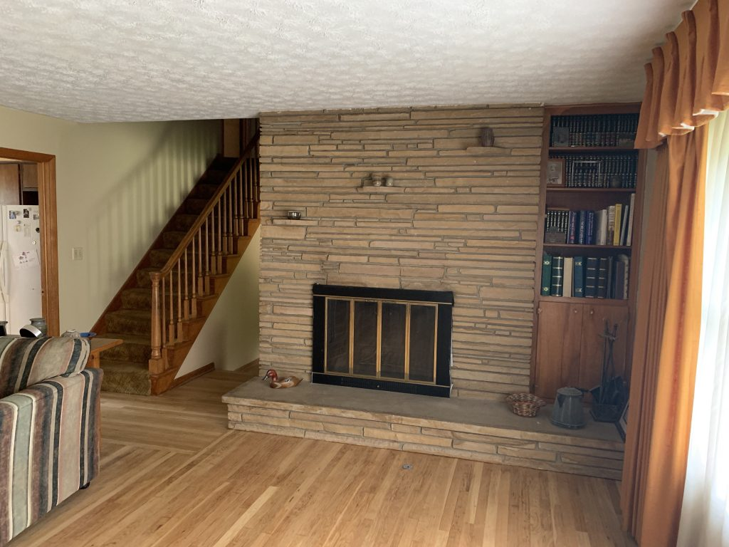 A living room hearth and wooden staircase.