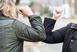 An elbow bump from two people in suits.