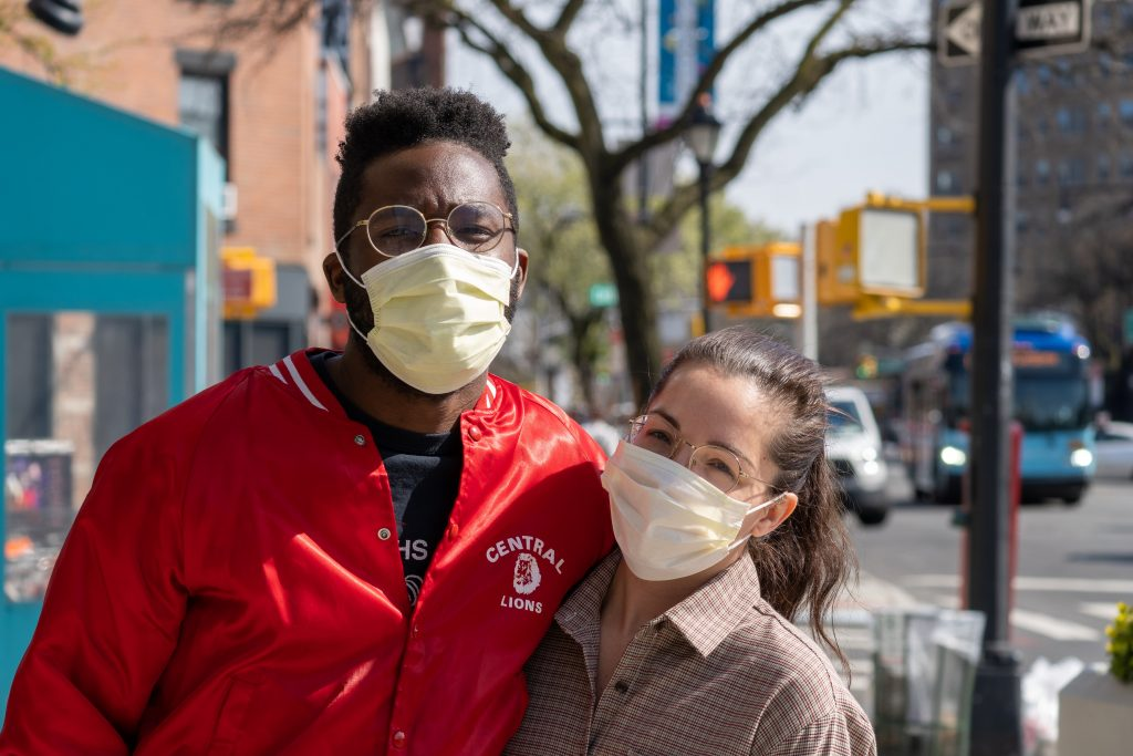 A couple with masks pose for a picture before moving out of the city during COVID.