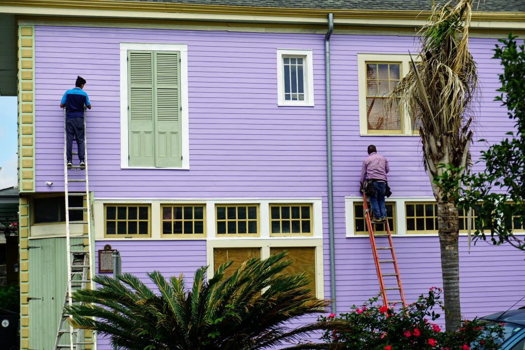 Two men on ladders painting the exterior of a purple building — one of the priciest home renovation costs there is.
