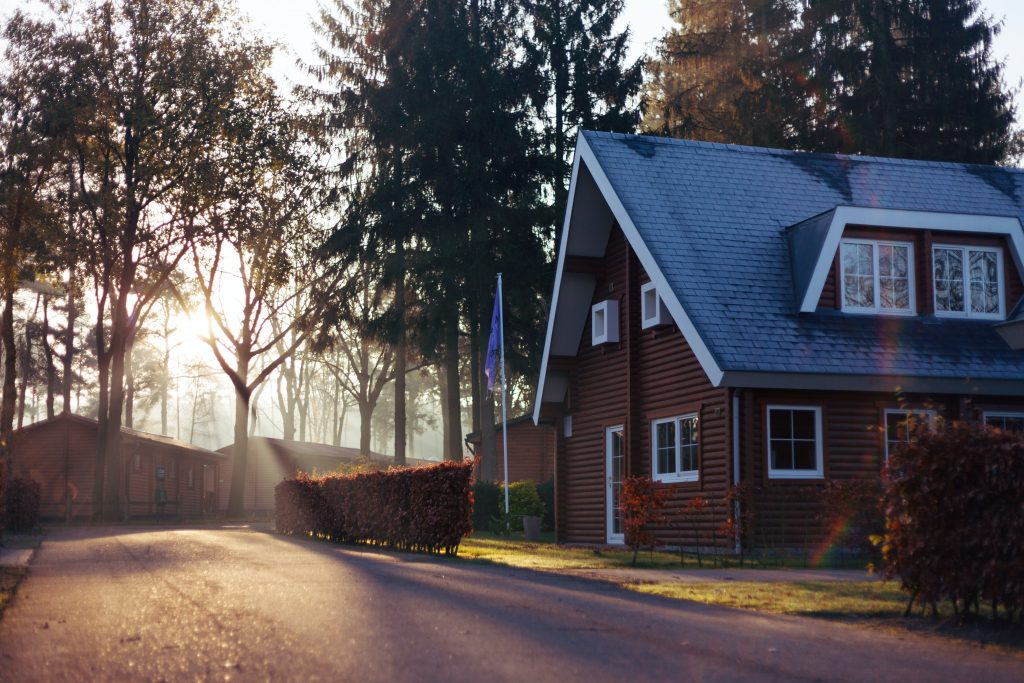 A beautiful home by a road surrounded by bushes and trees with a flag out front.
