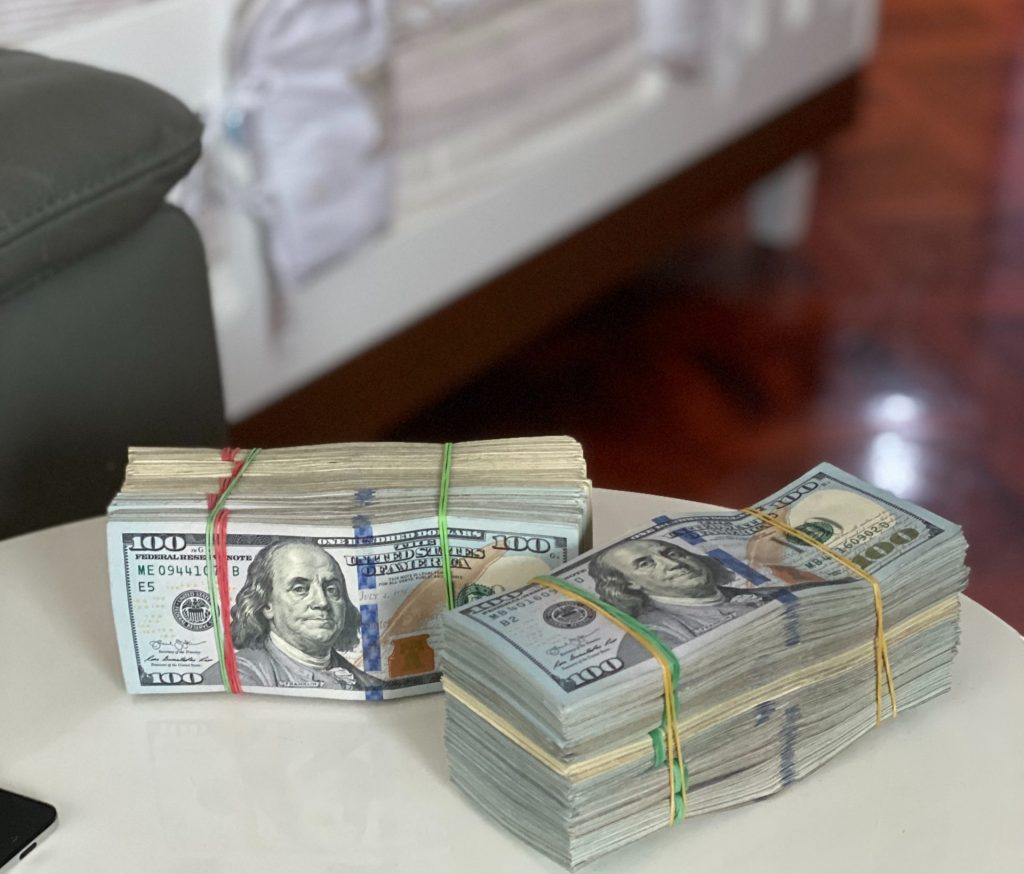 Two fat stacks of one-hundred-dollar bills on a table in a house.