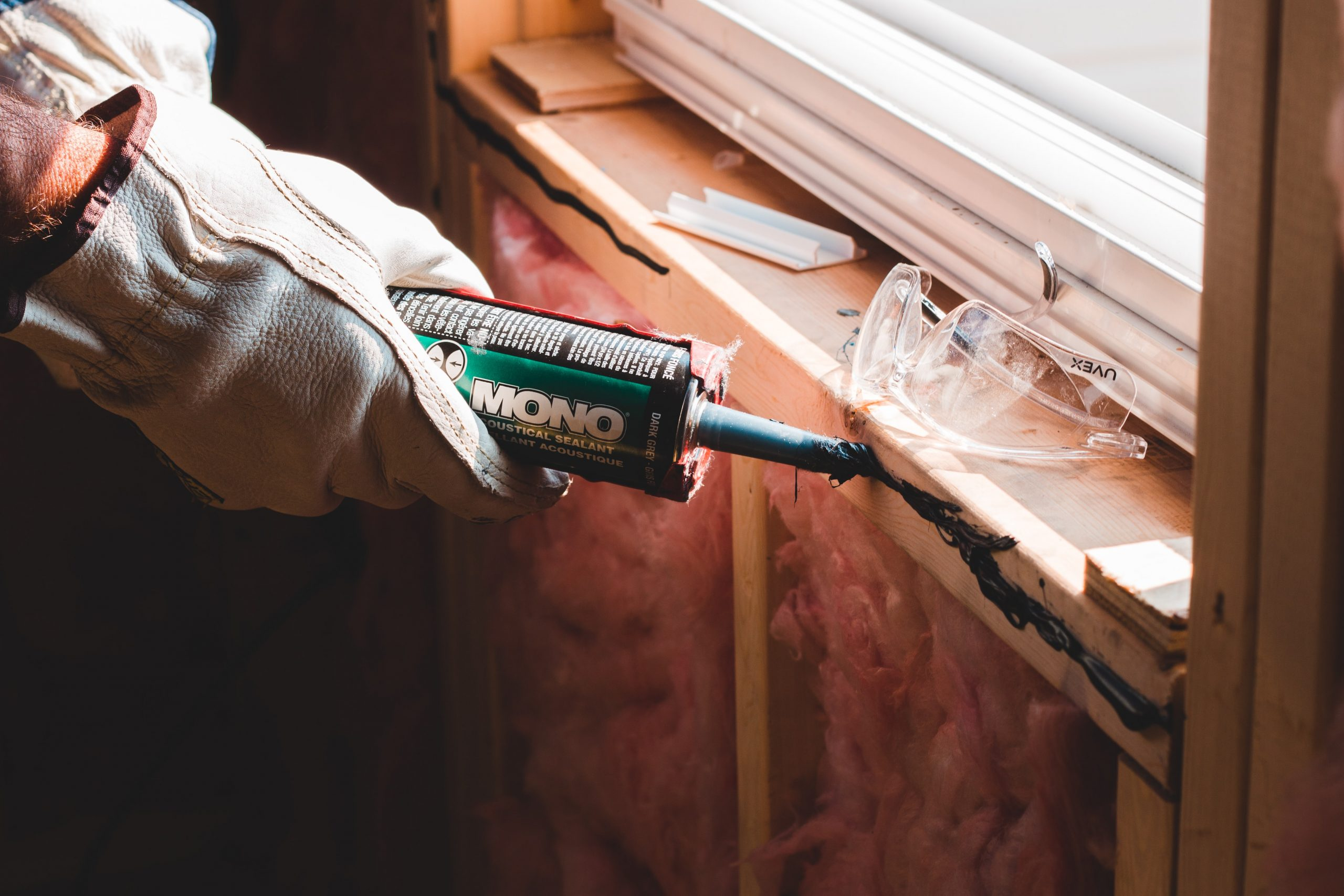 A person's gloved hands apply a tube of green Mono sealant to a window sill that is under construction.