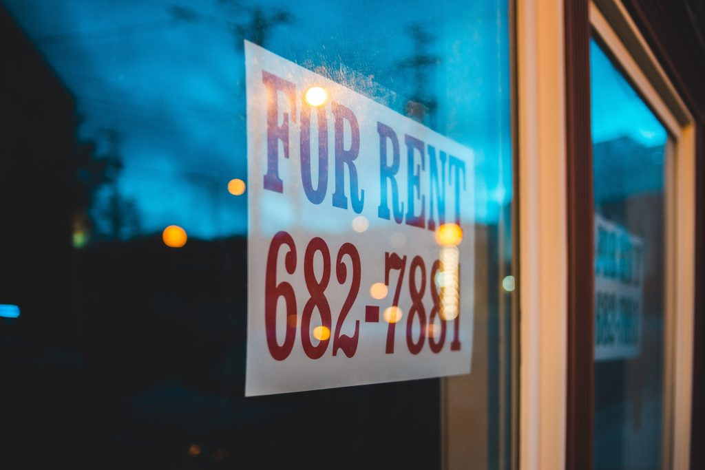 """""""For Rent"""" sign in a window with a number to call."""