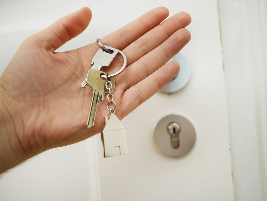 A hand holding a set of house keys with a house-shaped key ring attached.