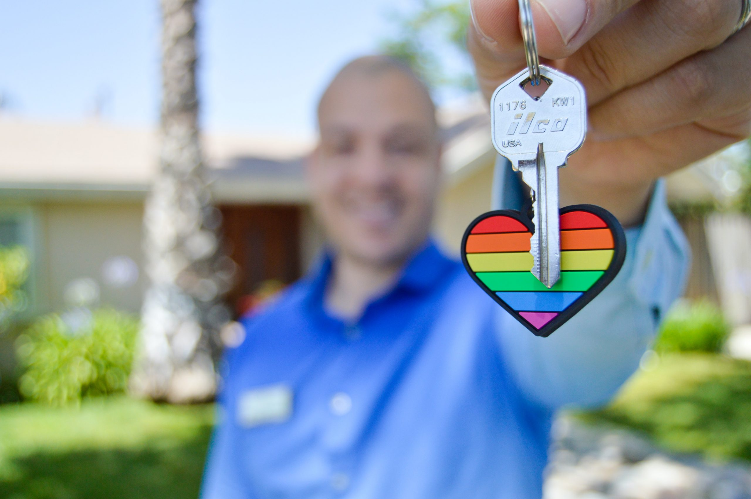 A man holding up a house key with a rainbow heart key ring on it.