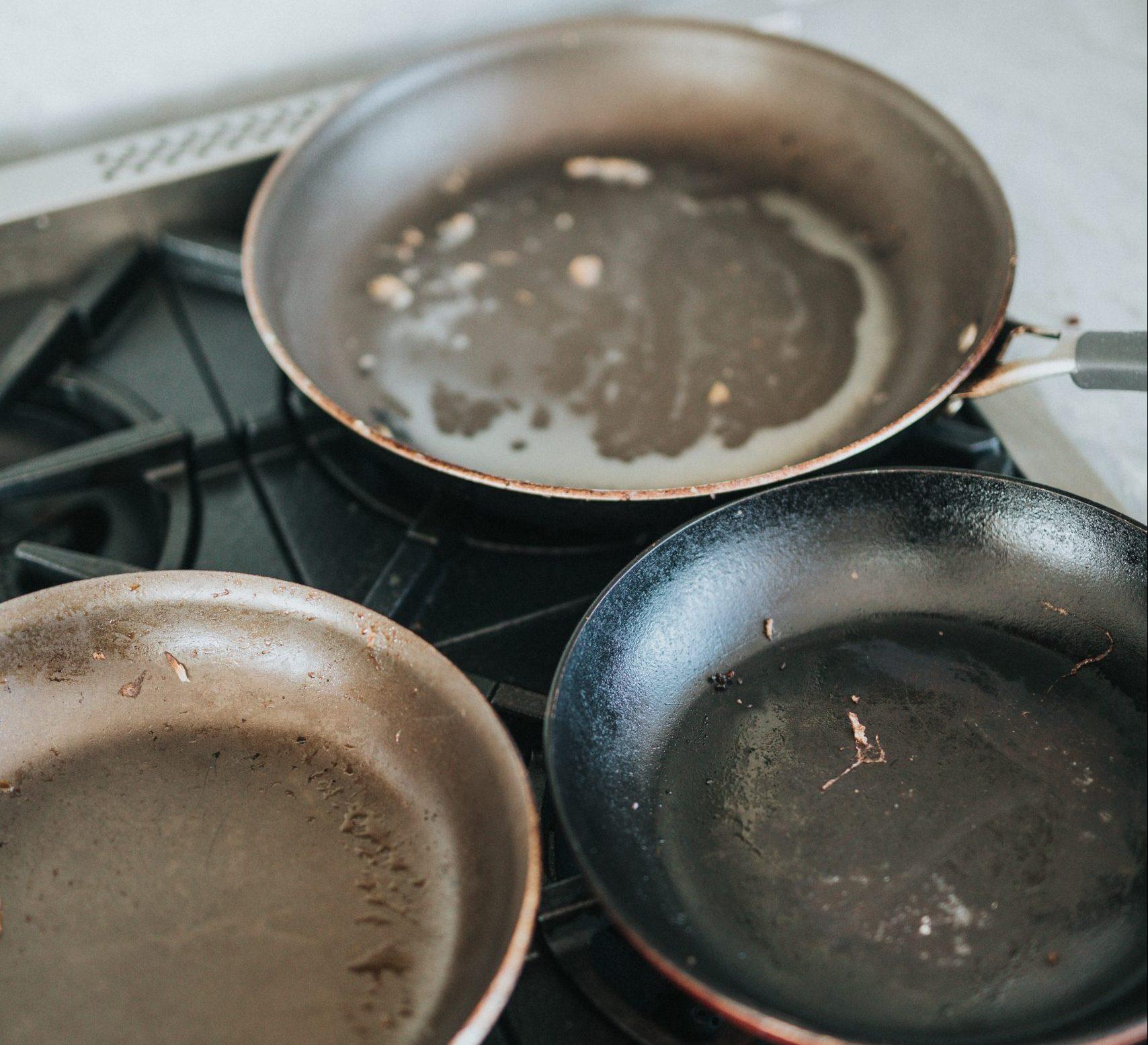 Three greasy pans on stove range.