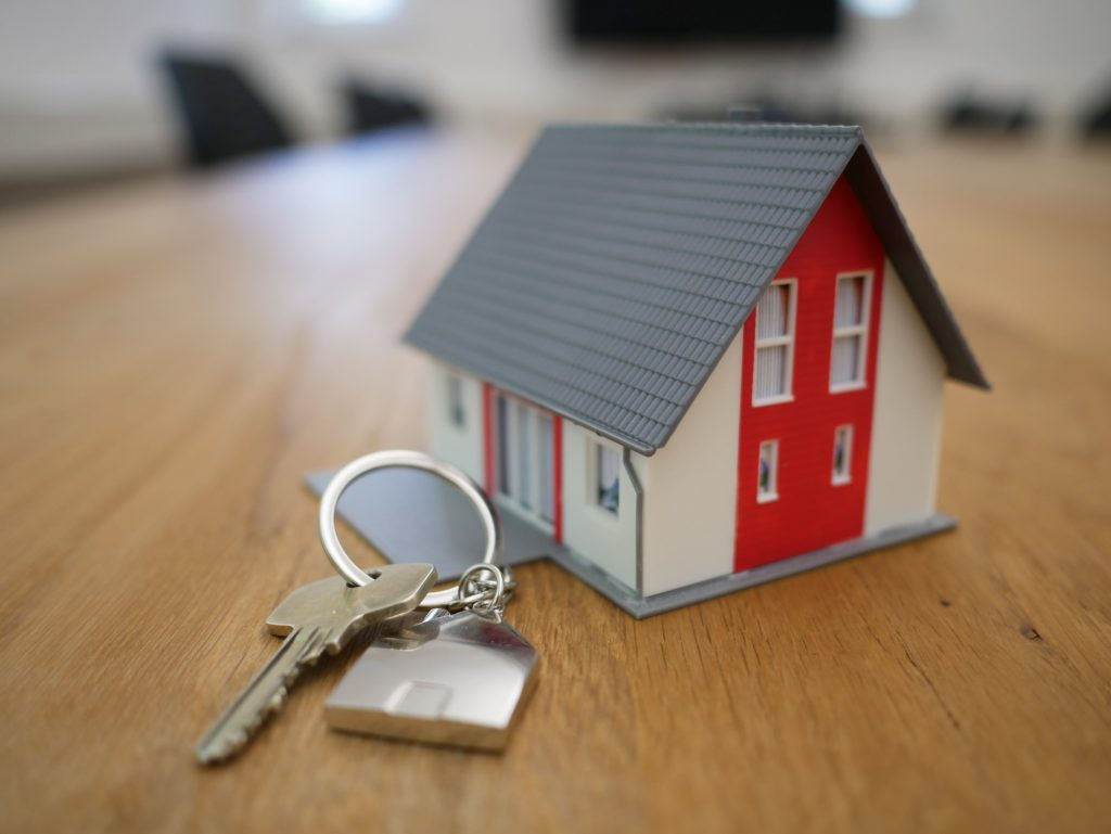 Miniature house with a set of keys on a wooden table.