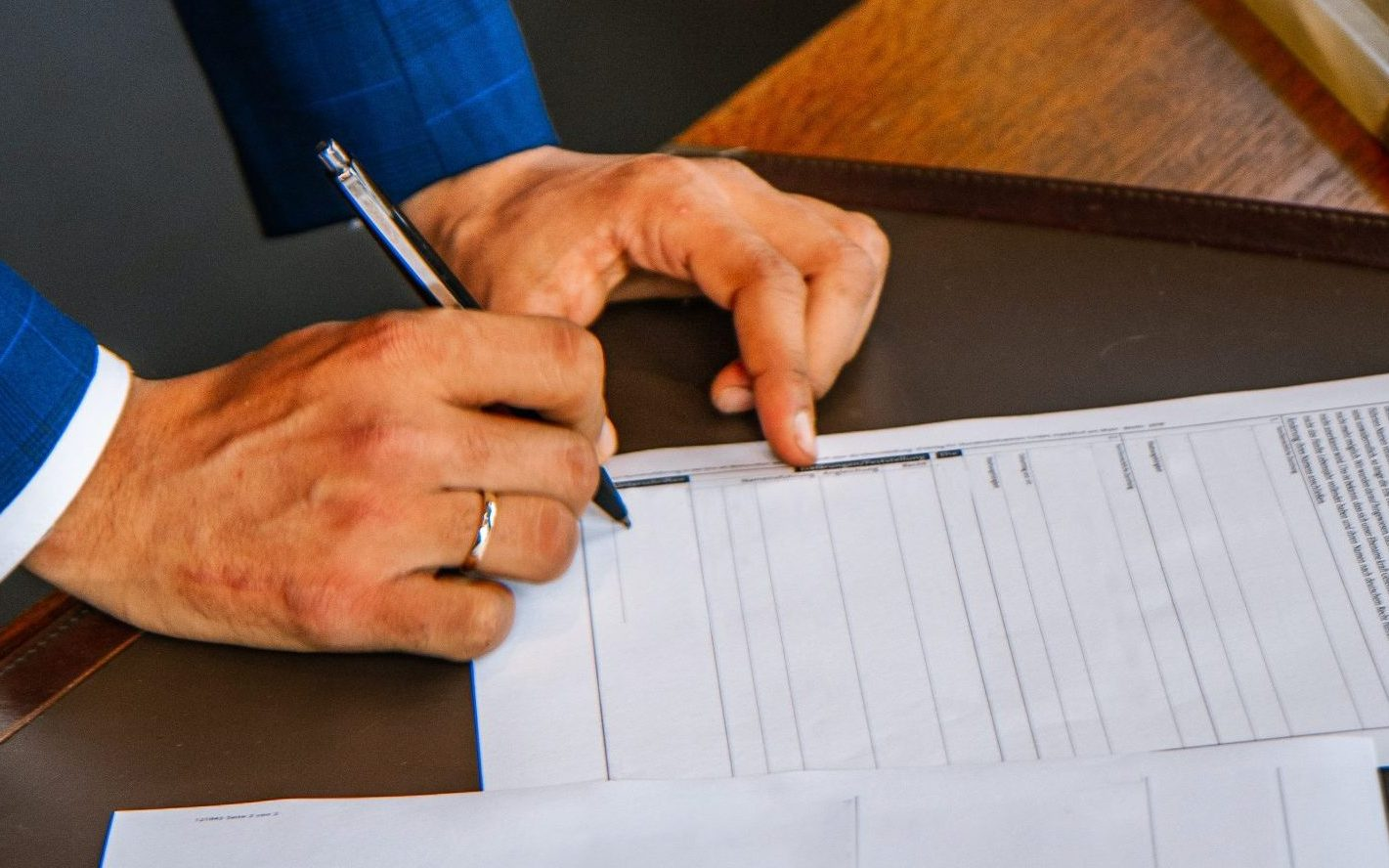 A man in a fancy blue suit writing with a pen on a contract.