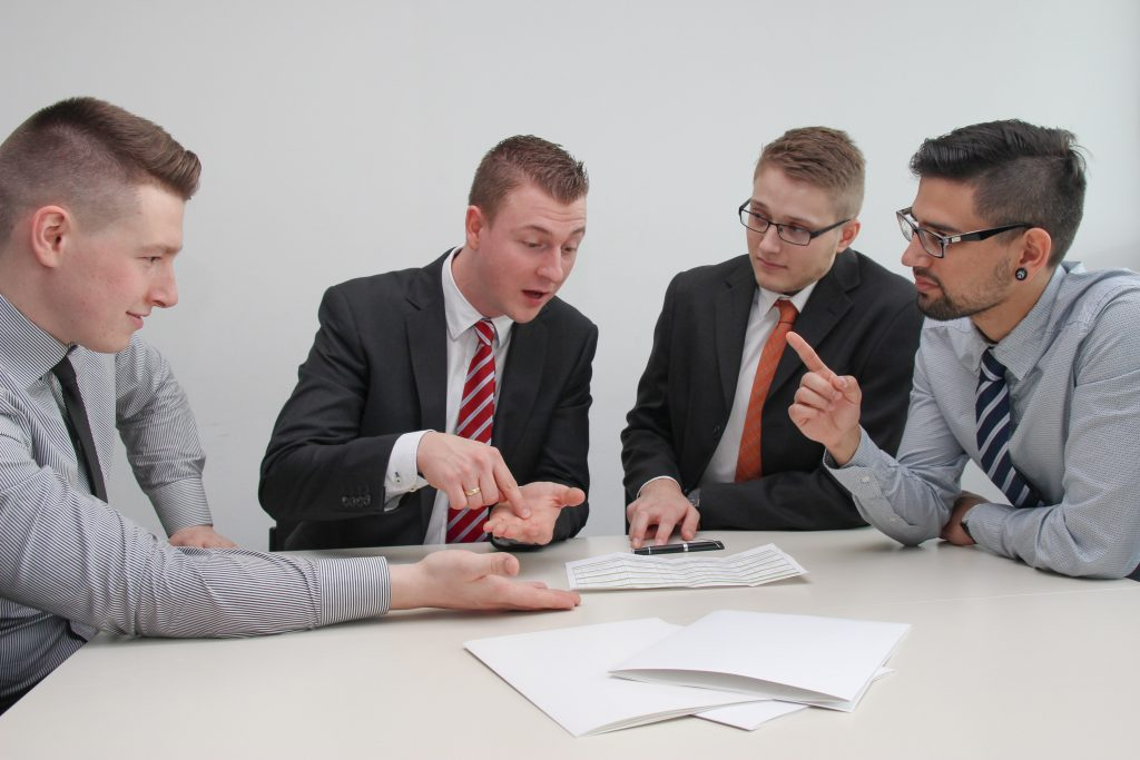 What does a title company do? It makes closing your home easier and safer as demonstrated by these four young men in business clothes and ties signing contracts on an eggshell white table.