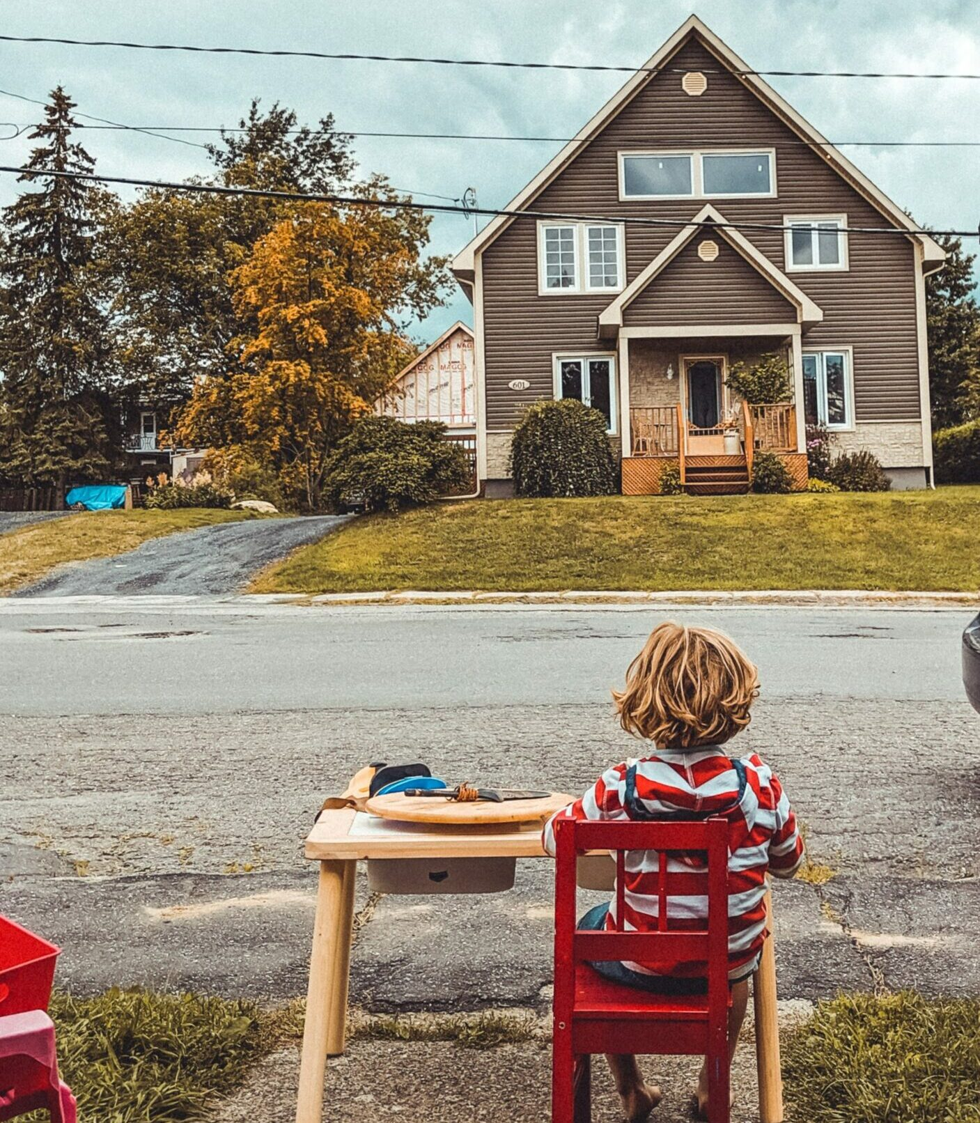 Young redheaded boy sitting at a wooden table across the street from a house.