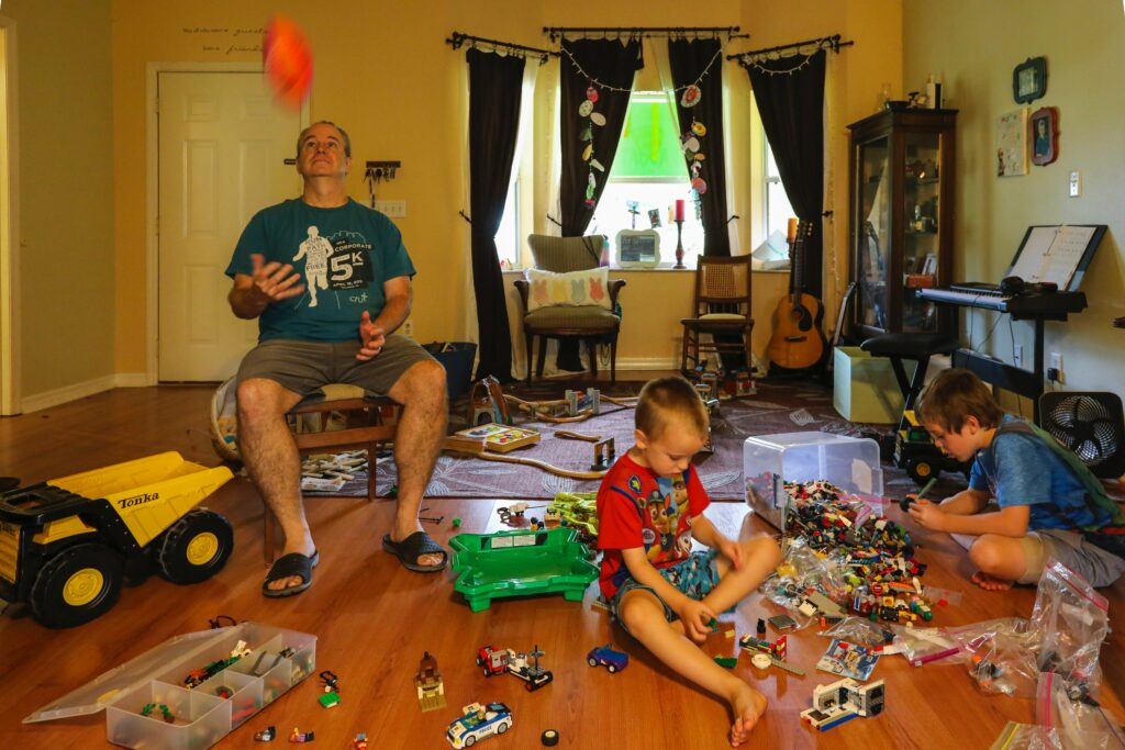 Two children and a man haven't learned how to prepare for a move as they sit playing with toys in a messy room.