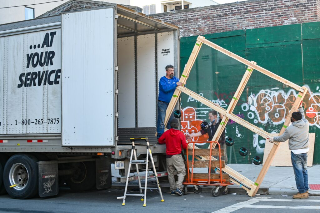 Four movers load a wooden bed frame onto a moving truck.