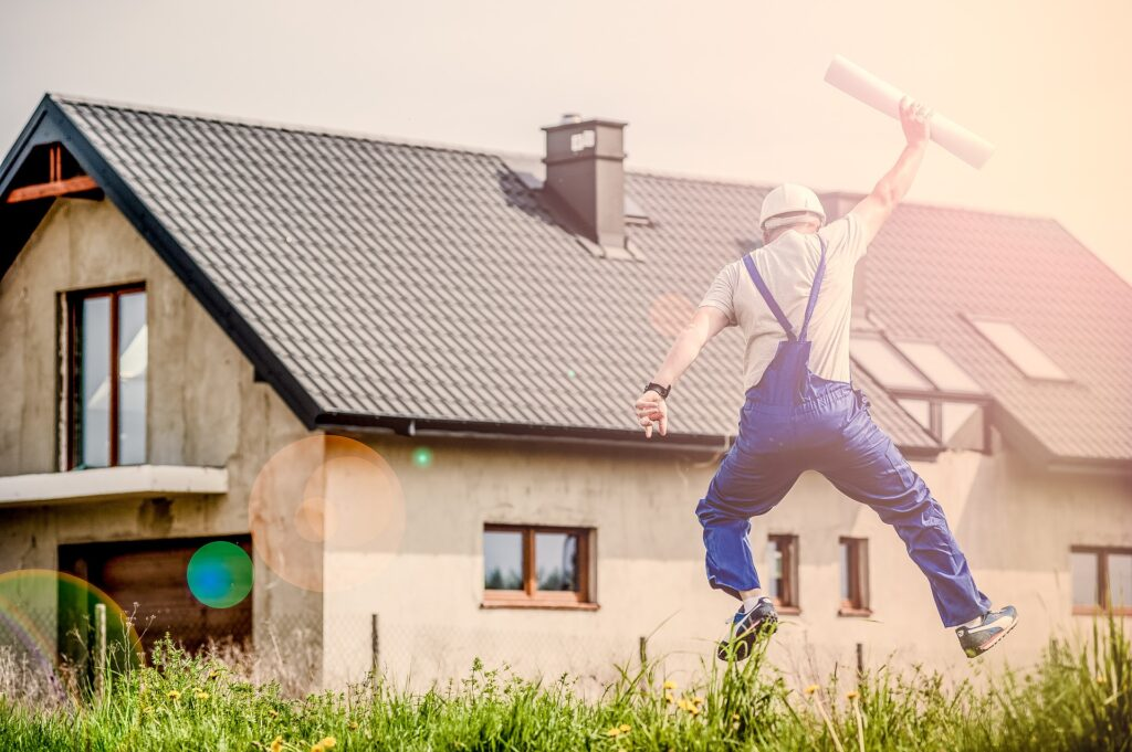 A man in blue overalls leaping in the air with a rolled up blueprint in his hand outside of a house.