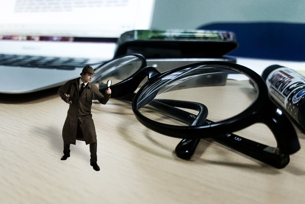 A miniature inspector holds a magnifying glass up to a pair of black eyeglasses.