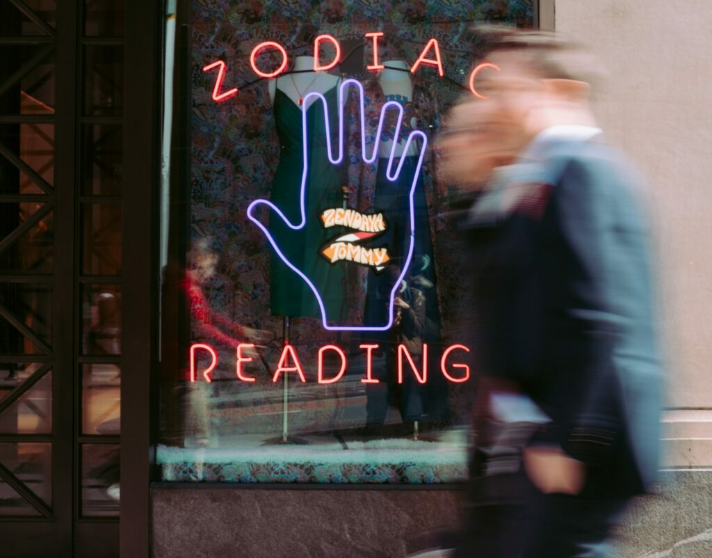 """Two men walk past a shop window with a neon sign with the words """"ZODIAC READING"""" around a neon purple hand."""
