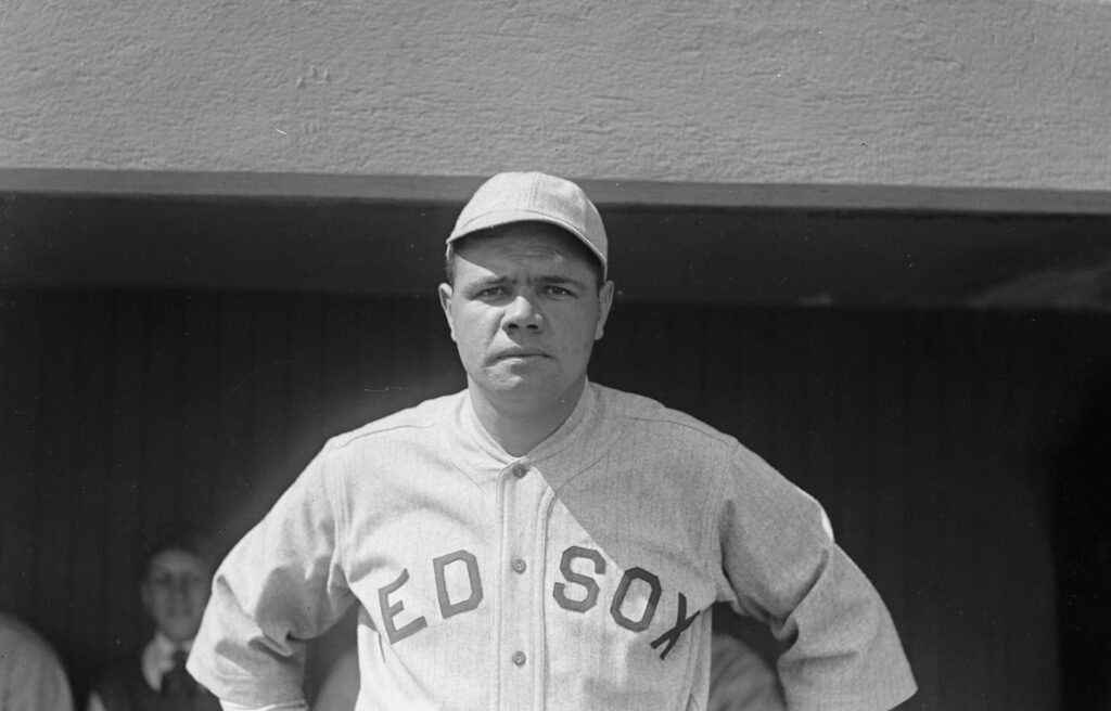 Babe Ruth in his Red Sox jersey with his hands on his hips.