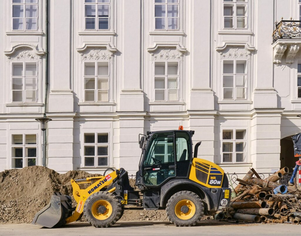 A yellow and black Komatsu bulldozer in front of an ornate off-white building.