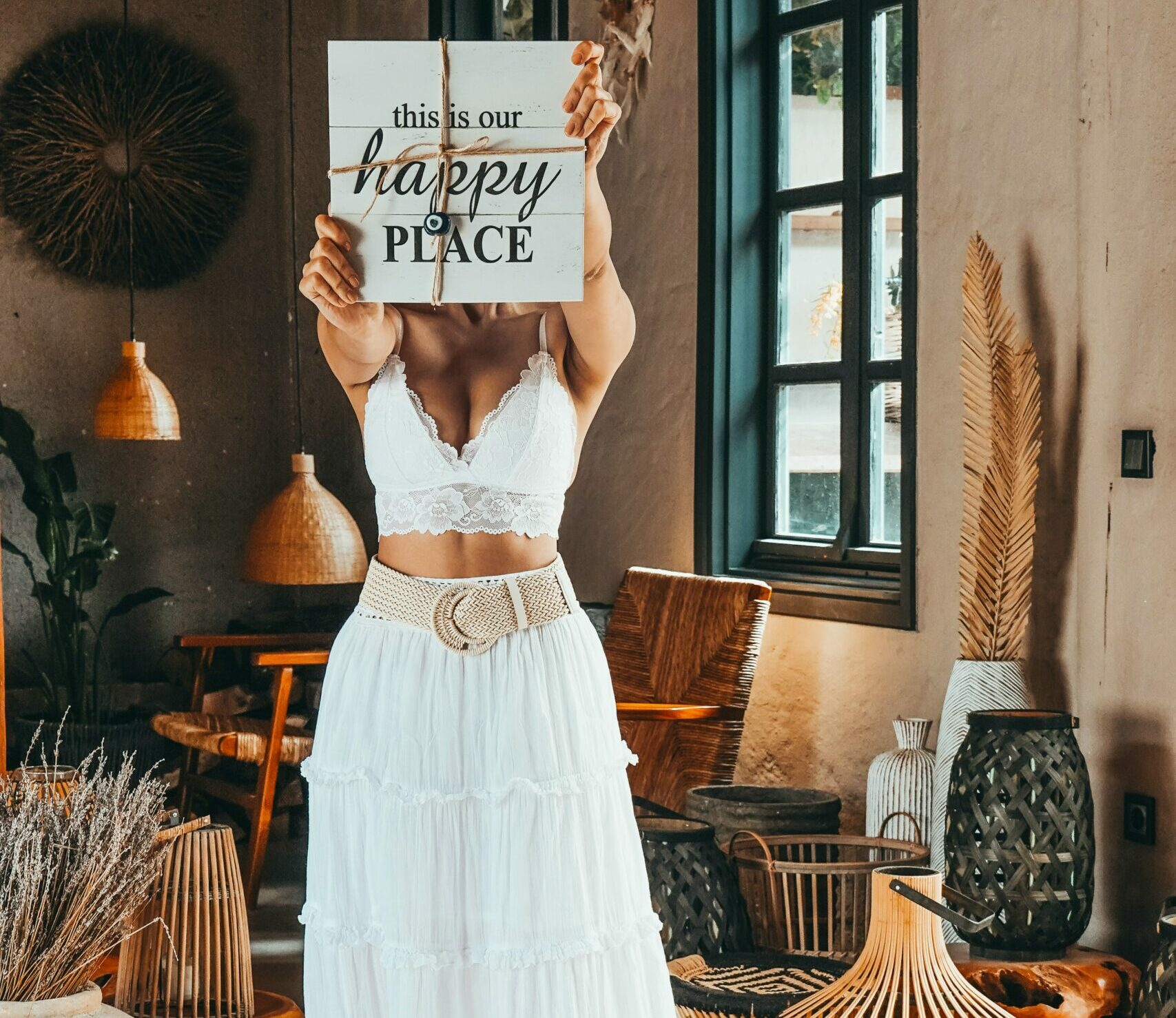 """A woman in a white dress holding up a sign that says, """"This is our happy place."""""""