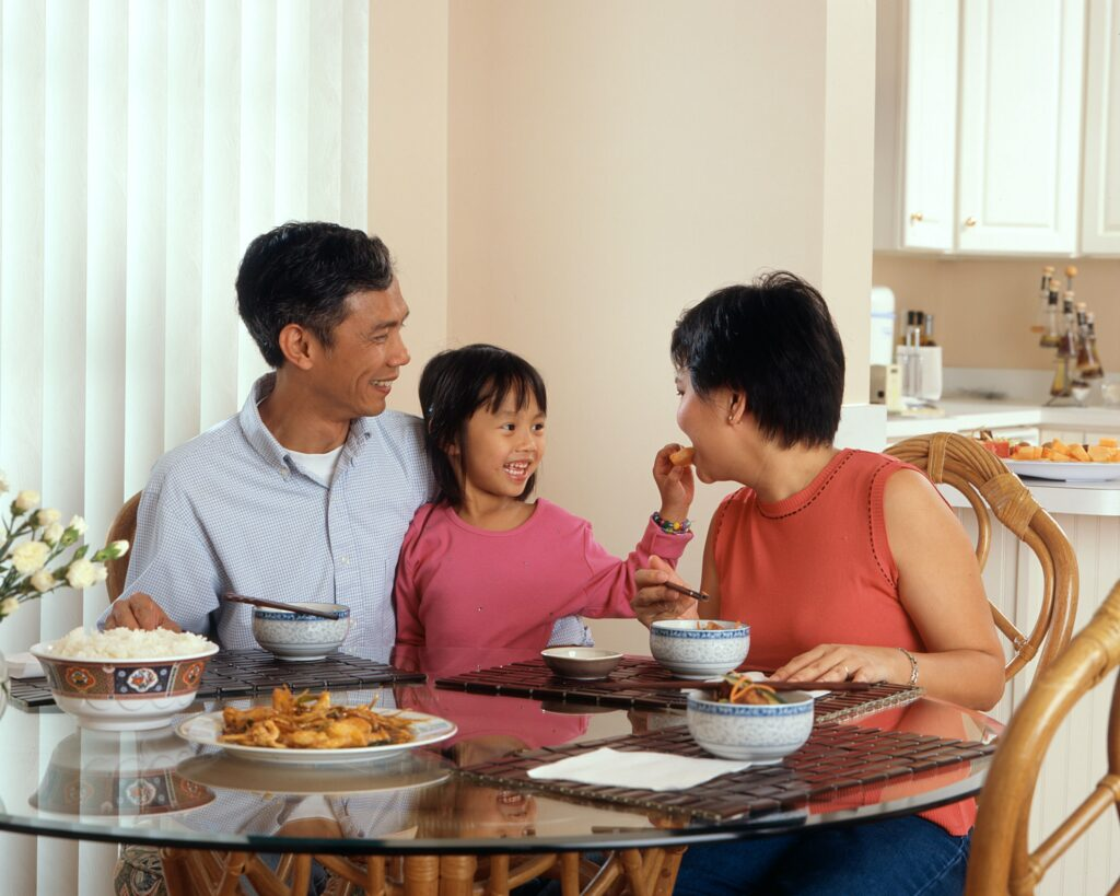 A family of three smiling at the breakfast table in a beautiful home.