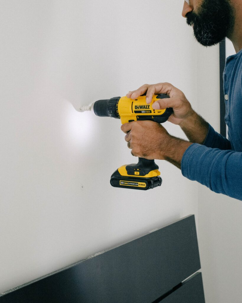 A man with a beard using a yellow DeWalt drill to drill into a white wall.