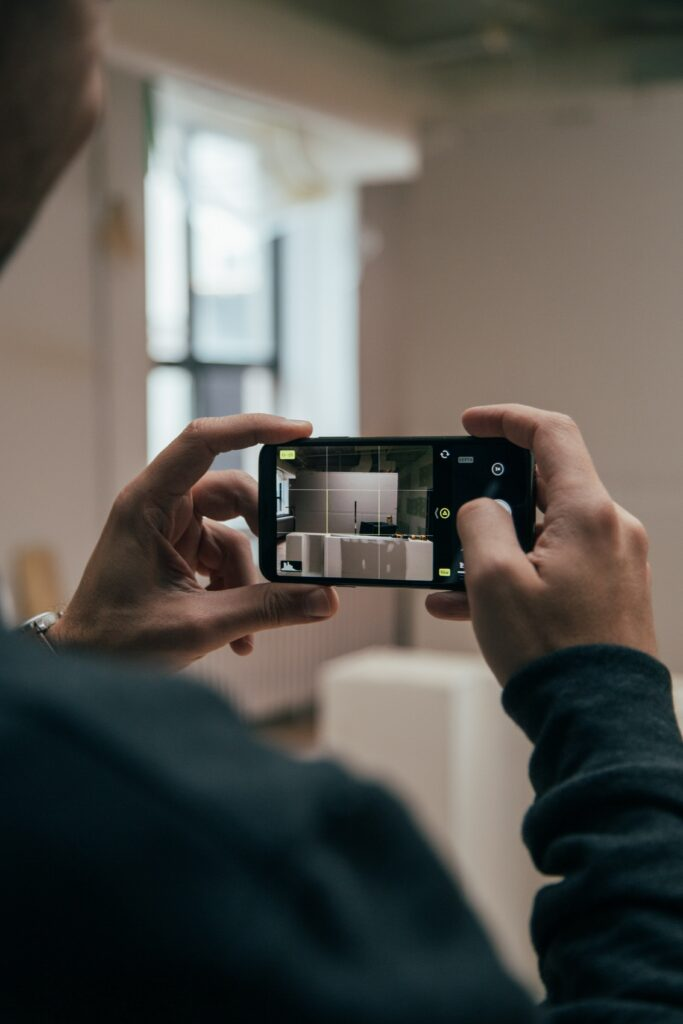 A man looking through a camera at the inside of a home.