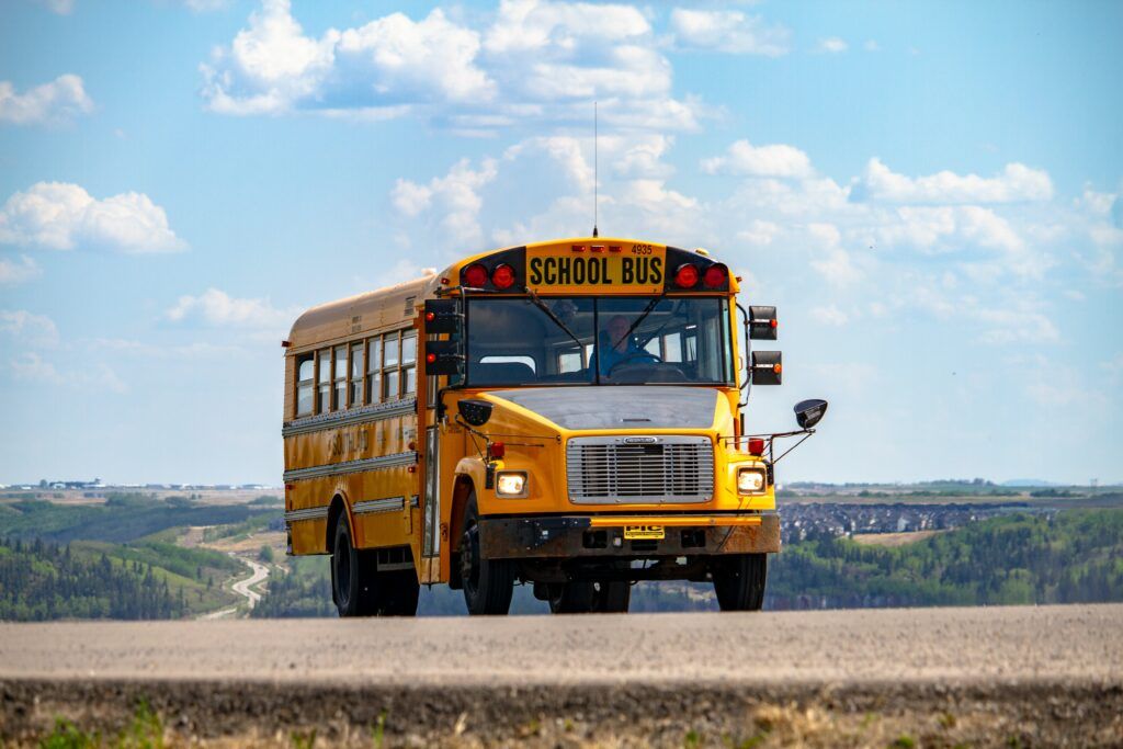 A school bus on the road under a blue sky and some fluffy clouds.