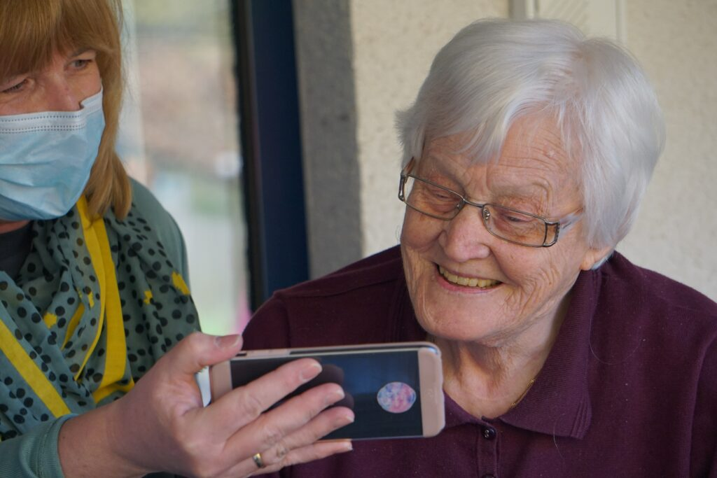 A senior woman smiles at a cell phone held in front of her by a masked woman.