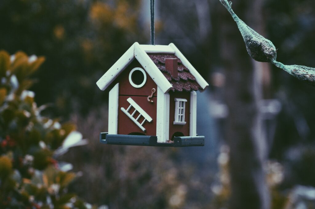 A tiny birdhouse hanging — proof that not everything sells in a hot house market.