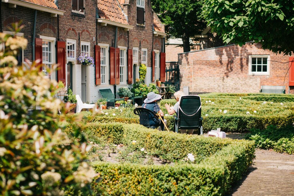 Two elderly folks sitting and chatting amongst shrubbery in a lovely outdoor area.
