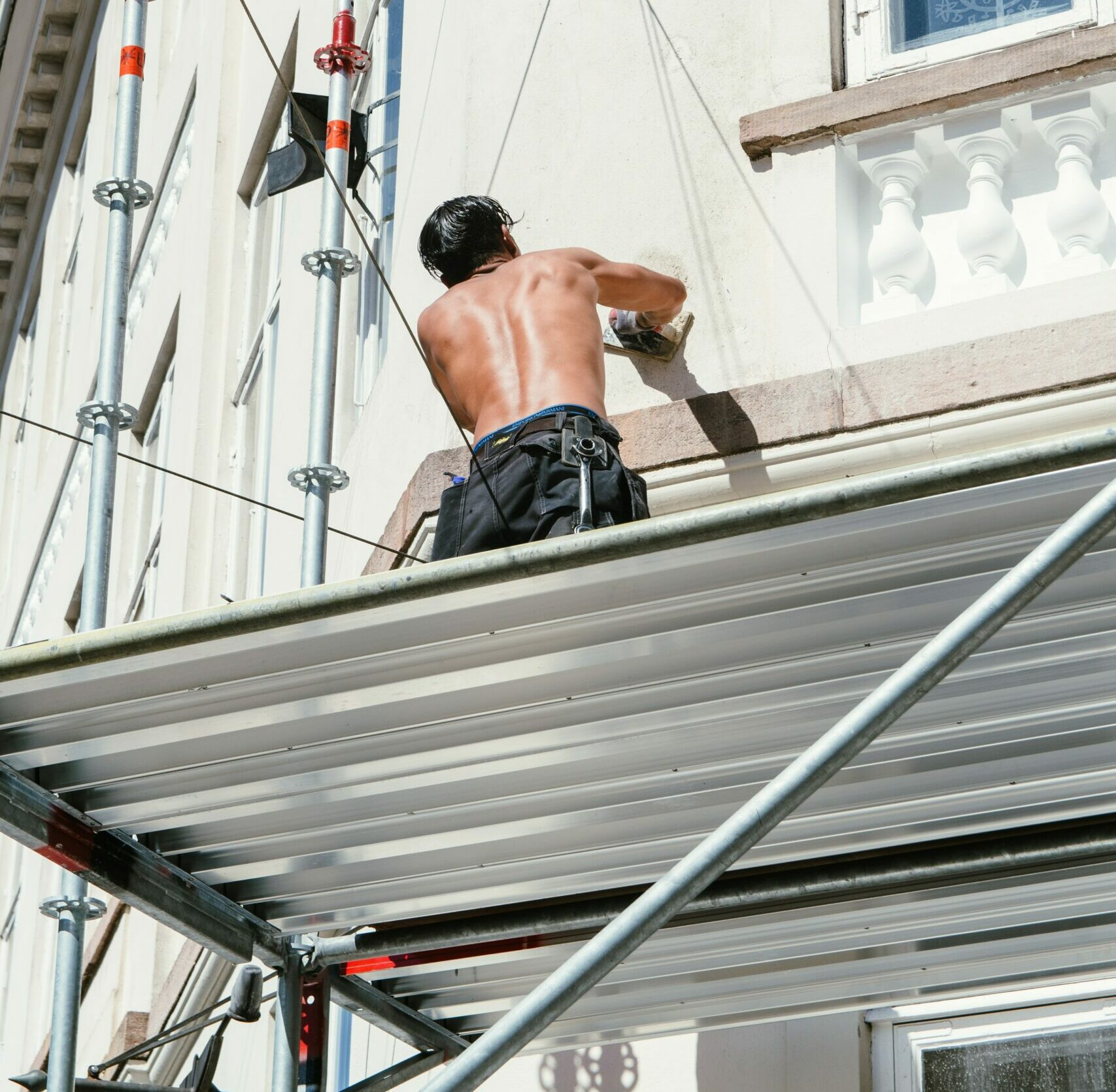 A shirtless man on scaffolding is working on the outside of a white house.