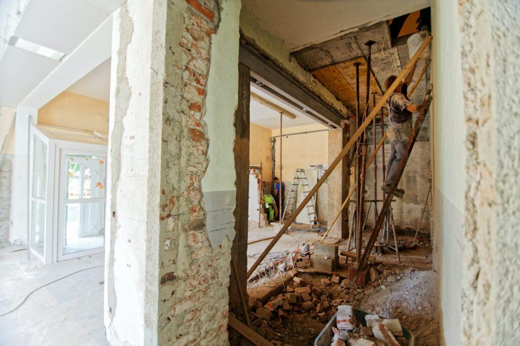 A man working on a ladder inside a torn-up home.
