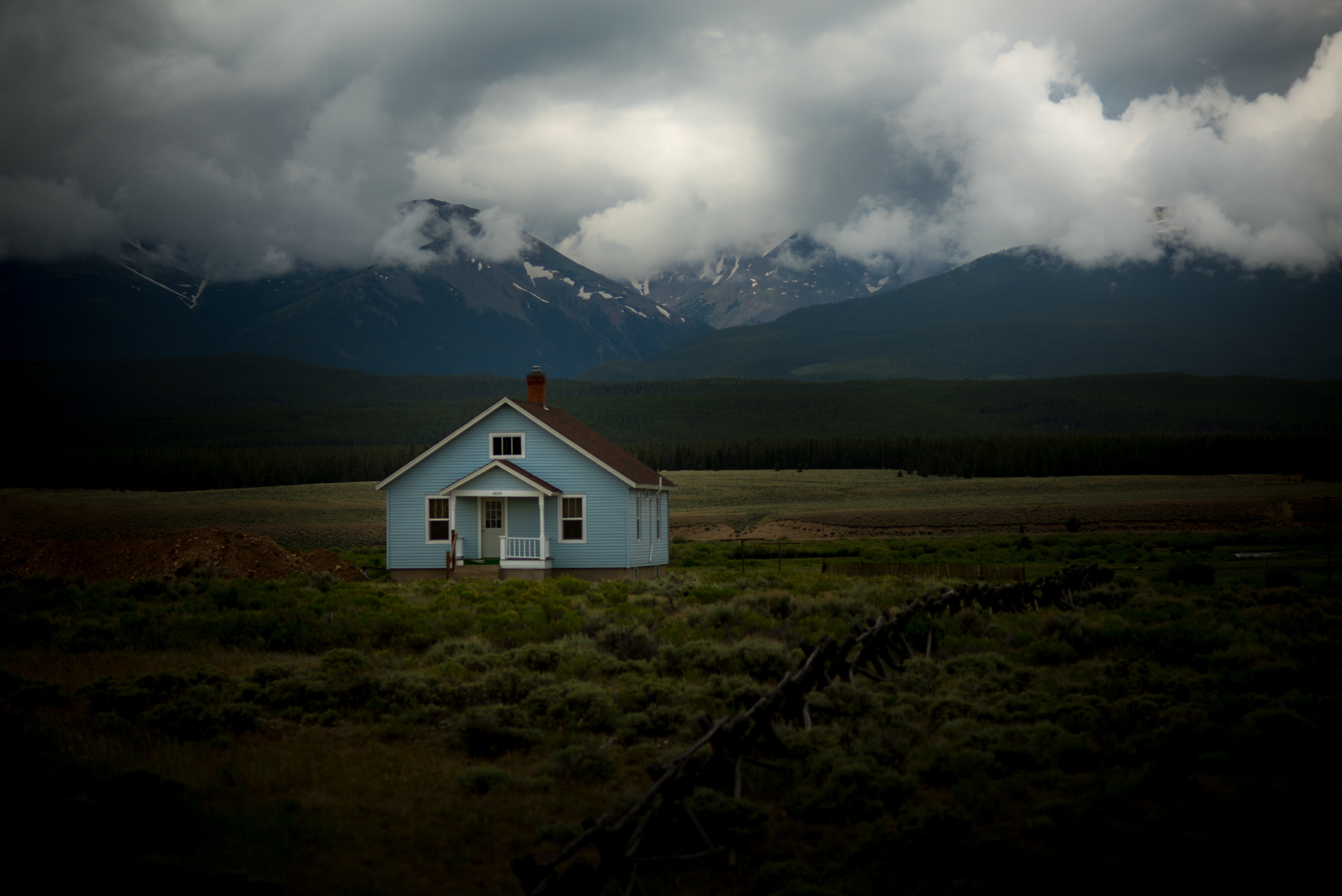 A small, baby blue house in the middle of a foggy field with snow-capped mountains in the distance.