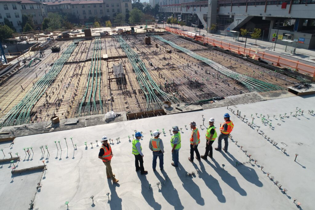 Seven construction workers standing on the roof of a building being built.