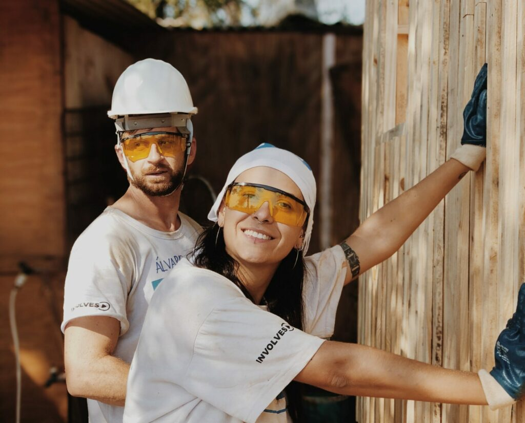 A man and a woman in hard hats working outside on a home renovation project.